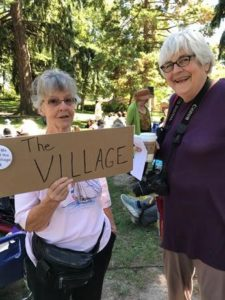 """Two women outside in a park, one holding a sign that says, """"The Village"""" referring to the PNA Village program."""
